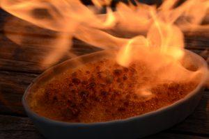 Crème brûlée mit Flamme des Bunsenbrenners
